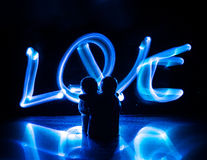 2 молодых любовника красят сердце на огне Силуэт пар и слов влюбленности на темной предпосылке Стоковое Фото