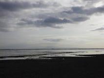 Молчаливый пляж с облаками стоковая фотография
