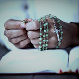 Моля руки женщины с розарием и библией Стоковое Изображение RF