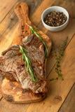 Мраморизованный стейк говядины на доске с перцем розмаринового масла, специями, на деревянной предпосылке, меню ресторана, гастро стоковые фото