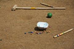 Мраморные шарики на предпосылке песка Мушкел крокета Играть оборудование детей Стоковое фото RF