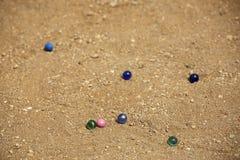 Мраморные шарики на предпосылке песка Мушкел крокета Играть оборудование детей Стоковые Фотографии RF