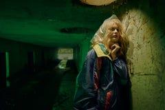 Мрачный портрет модели представляя в реке нечистот в тоннеле под городом Lit с зеленым светом Стоковые Изображения RF
