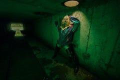 Мрачный портрет модели представляя в реке нечистот в тоннеле под городом Lit с зеленым светом Стоковое фото RF