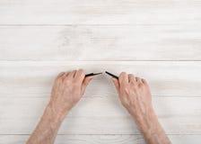 Мужеские руки сломали черный карандаш в взгляд сверху стоковые фотографии rf