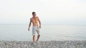 Мужеский человек тела в солнечных очках на пляже с mountauns на предпосылке сток-видео