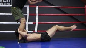 Мужская высокорослая тренировка боксера с тренером Парень спорт лежа на поле на боксерском ринге и делая тренировки ног с видеоматериал