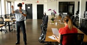 Мужская исполнительная власть используя шлемофон виртуальной реальности пока его коллега работая на столе 4k видеоматериал