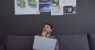 Мужская исполнительная власть работая на ноутбуке в современном офисе 4k сток-видео