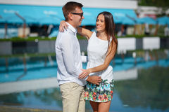Мужская и красивая женщина в белом платье смотрит один другого на курорте Пара падени-в-влюбленности идет outdoors Стоковые Изображения RF