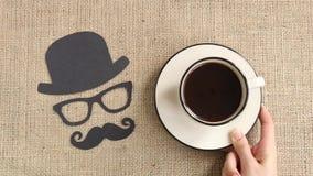 Мужская картина силуэта с усиком, стеклами и шляпой с чашкой кофе на предпосылке мешковины