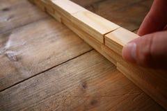 мужская кирпичная стена здания руки от деревянных блоков домино Стоковое Изображение