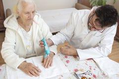Мужская медсестра кладет сливк на руку старухи Косметические обработка и уход стоковые фотографии rf