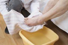 Мужская медсестра обтирает ноги старухи полотенцем стоковое изображение