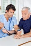 Мужская медсестра проверяя кровяное давление старшего человека стоковое фото