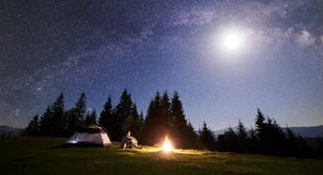 Мужская ноча enjoyng hiker располагаясь лагерем около туристского шатра на лагерном костере под голубыми звёздными небом и млечны стоковые фотографии rf