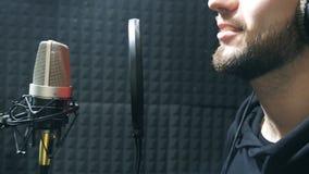 Мужская певица в наушниках поя песню в микрофон на ядровой студии Молодой человек эмоционально записывая новую песню видеоматериал