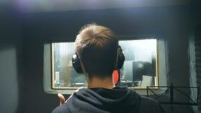 Мужская певица в наушниках поя песню на ядровой студии Непознаваемый молодой человек эмоционально записывая песню Деятельность  сток-видео