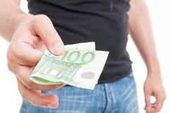 Мужская рука давая 100 евро Стоковые Фотографии RF