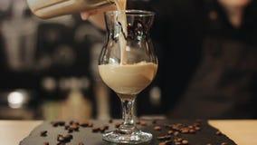 Мужская рука бармена лить напиток кофе в стекло тюльпана сток-видео