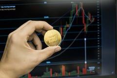 Мужская рука бизнесмена держа монетку черточки на предпосылке диаграммы роста на экране компьтер-книжки Виртуальные деньги и стоковое фото