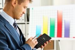 Мужская рука в калькуляторе владением костюма отжимая кнопки Стоковое Изображение RF