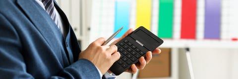 Мужская рука в калькуляторе владением костюма отжимая кнопки Стоковые Фотографии RF