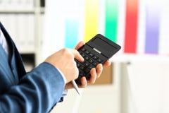 Мужская рука в калькуляторе владением костюма отжимая кнопки Стоковое фото RF