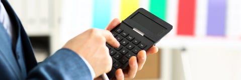 Мужская рука в калькуляторе владением костюма отжимая кнопки Стоковые Изображения