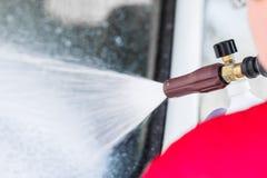 Мужская рука в перчатке держа прибор для распыляя пены мытье губки машины шланга автомобиля чистое Стоковые Фото
