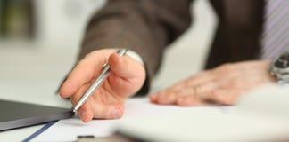 Мужская рука в ручке владением костюма и связи серебряной стоковые изображения