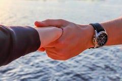 Мужская рука держа женскую руку с предпосылкой воды стоковая фотография rf