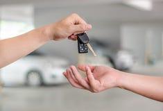 Мужская рука держа ключ и вручать автомобиля Стоковое Изображение