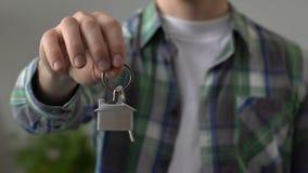 Мужская рука держа конец-вверх дома ключевой цепи, ссуду под недвижимость, ренту квартиры видеоматериал