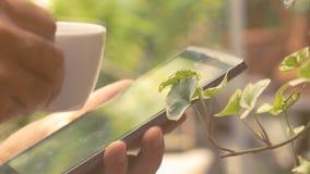 Мужская рука держа кофейную чашку и используя таблетку цифров сток-видео