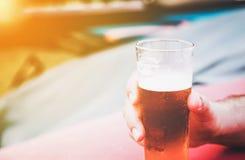 Мужская рука держа малое стекло холодного пива Стоковая Фотография