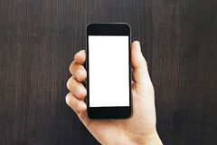 Мужская рука держа пустой белый телефон стоковые изображения rf