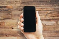 Мужская рука держа пустой мобильный телефон стоковая фотография