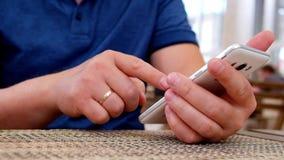 Мужская рука держа Smartphone, в кафе акции видеоматериалы