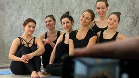 Мужская рука держа smartphone принимая фото группы в составе девушки в классе фитнеса на пролом Стоковые Фото