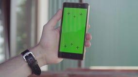 Мужская рука держа smartphone с зеленым экраном видеоматериал