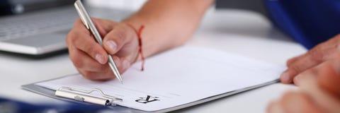 Мужская рука доктора пишет рецепт на офисе Стоковое Изображение RF