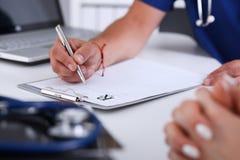 Мужская рука доктора пишет рецепт на worktable офиса Стоковое Изображение