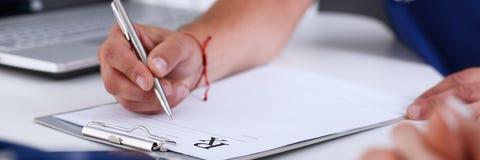 Мужская рука доктора пишет рецепт на worktable офиса Стоковое Фото