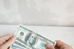 Мужская рука держа 100 банкнот доллара Стоковая Фотография