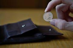 Мужская рука держа бронзовую монетку 10 иен японских иен, JPY и разделяя то от кожаного бумажника Стоковая Фотография