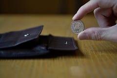 Мужская рука держа бронзовую монетку 10 иен японских иен, JPY и разделяя то от кожаного бумажника Стоковые Изображения