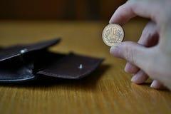 Мужская рука держа бронзовую монетку 10 иен японских иен, JPY и разделяя то от кожаного бумажника Стоковое Изображение RF