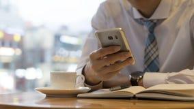 Мужская рука держа готовой сделать примечание, смотря мобильный телефон Идея дела сочинительства рабочего места бизнесмена или ра стоковое фото