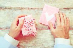 Мужская рука держа карточку и подарок Стоковое фото RF